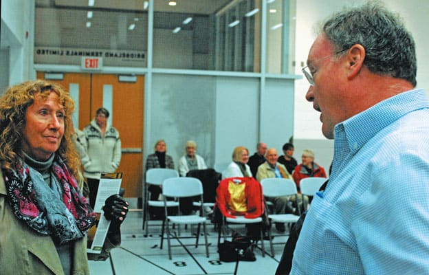 Ward 1 candidate Sebastian Siebel-Achenbach speaks with resident Brenda Kempel, who pressed for a format change to allow for a proper public forum at Tuesday night's event in Elmira.[Steve Kannon / The Observer]