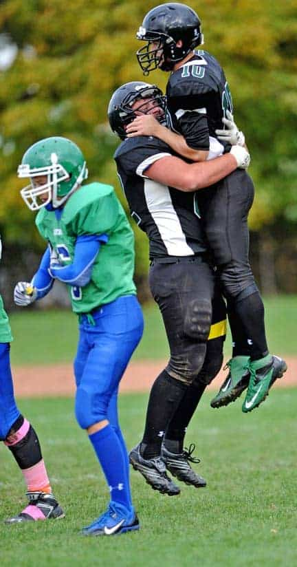 David Martin embraces senior Lancers quarterback Jordan Frey after the pivot ran in for a touchdown during the squad's 44-16 drubbing of the Celtics on October 10 in Elmira. [Scott Barber / The Observer]