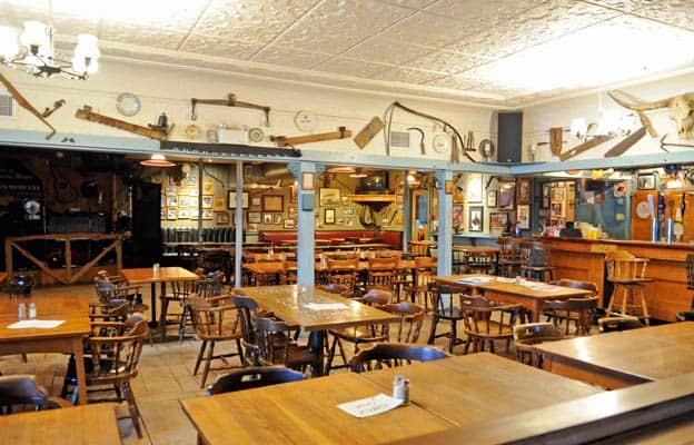 The walls are covered with historic photos, rustic tools, and old instruments, which give the bar its unique charm.