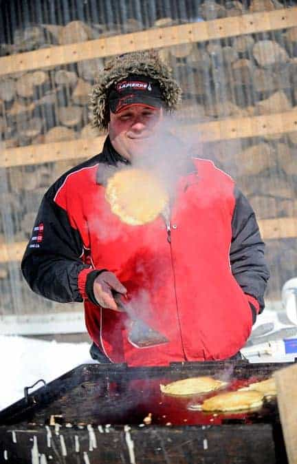 Local syrup producer Dale Martin flips a pancake at the ceremonial first tap event hosted by the Ontario Maple Syrup Producers' Association and the Elmira Maple Syrup Festival at George Martin's sugar bush just south of Heidelberg on Feb. 27. [Scott Barber / The Observer]