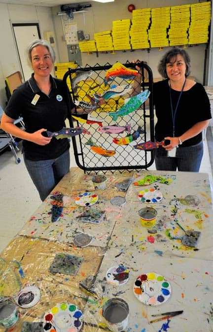 """Grand River Conservation Authority representative Jenn Deter and teacher Wendy Rudd are teaching Breslau Public School students about the importance of the local watershed with the """"Stream of Dreams"""" art project, which will see over 600 hand-crafted and painted fish installed along the school's fencing this week. [Scott Barber / The Observer]"""