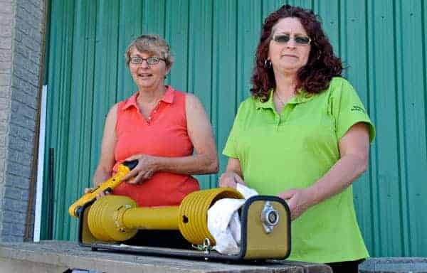 Waterloo Rural Women board members Sharon Grose and Susan Martin use a power take-off safety device in preparation for the 20th annual farm safety day June 13 in Wallenstein. [Scott Barber / The Observer]