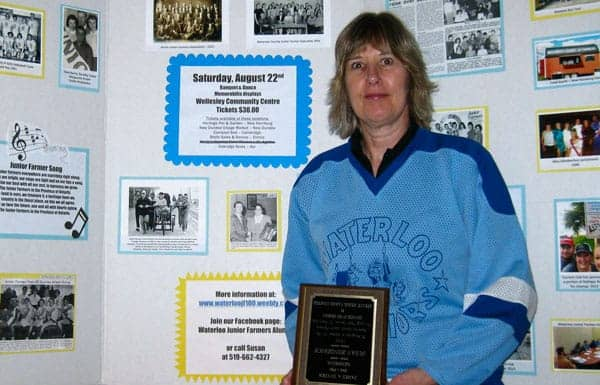 Susan Mills shows off one of the boards that will be on display at the Waterloo Junior Farmers' 100th anniversary celebration, along with the James A. Snyder award she received in 1992 to recognize her long term service to the club.  [Submitted]