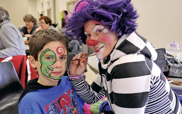Connor Niven, 7, gets a green lizard painted on his face by Kricket and Krew at Linwood Snofest on Saturday afternoon. The day started with a hearty breakfast served up by local firefighters, and the ever-popular sno-pitch tournament.[Liz Bevan / The Observer]