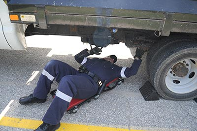 Staff Sgt. Michael Hinsperger double checks the brakes and the tires on a commercial vehicle pulled over during the commercial vehicle blitz in St. Clements on Wednesday morning. [Liz Bevan / The Observer]