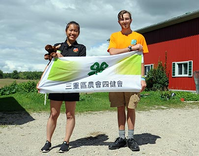 Ruby, or Hsu Ning Jui, and Andrew Grose from Alma pose with a Taiwanese 4-H flag at the Grose farm in Alma. The two participated in an international farming exchange with the 4-H Canada Going Global program.[Liz Bevan / The Observer]