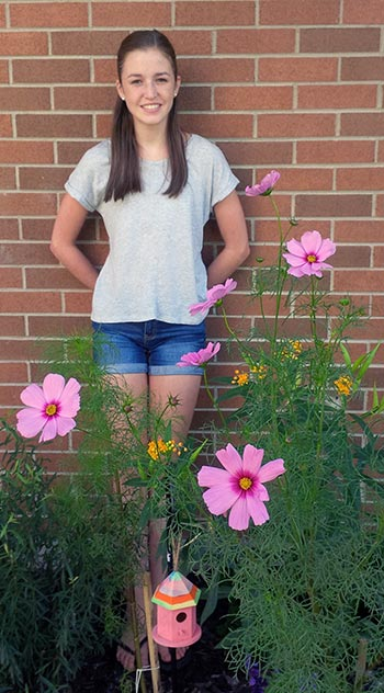 Having graduated from the school, Sarah Lucier still finds time to tend to the butterfly garden she created at St. Teresa Catholic school in Elmira.[submitted]