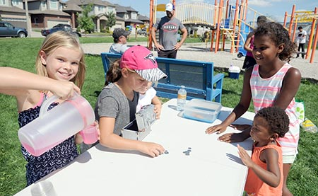 Olivia Jennex, 9, pours some lemonade at their bracelet, cookie and lemonade stand in Breslau while Ava Wales, 7, counts the cash, serving their neighbourhood friends for a good cause.[Liz Bevan / The Observer]