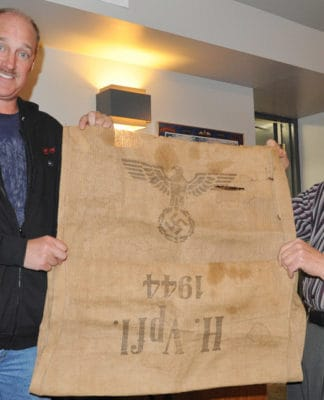 A simple burlap food bag emblazoned with the Nazi symbol makes its way to the Elmira Legion