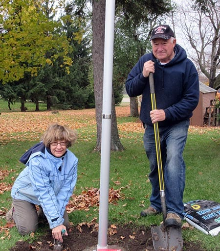 Charlene & Tom Schell planting the Canada 150 Anniversary Commemorative Tulip Bulbs around the flag pole at the Edward Halter Home