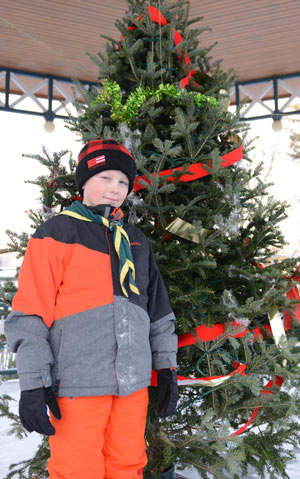 Scout Zain Wilson stands in front a decorated Christmas tree at the bandstand in Elmira's Gore Park, where the 1st Elmira Scouts are selling Christmas Trees once again for their annual fundraiser.